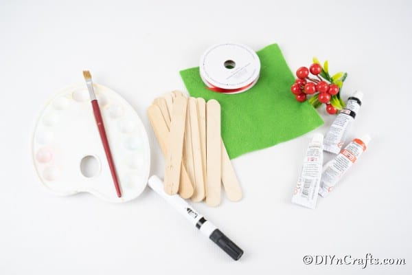 Supplies for making popsicle stick snowman laying on a table