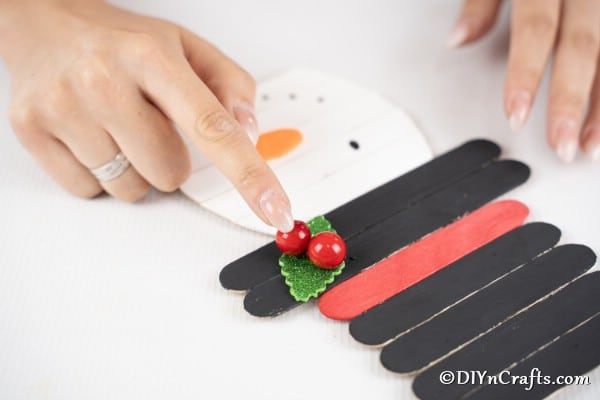 Adding the greenery and berries to the top of the craft stick snowman decoration hat.