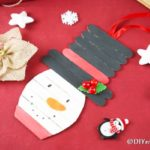 Snowman popsicle stick craft on red paper