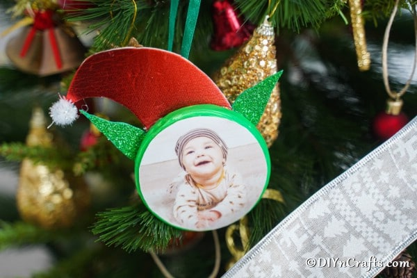 Elf photo ornament hanging on a Christmas tree