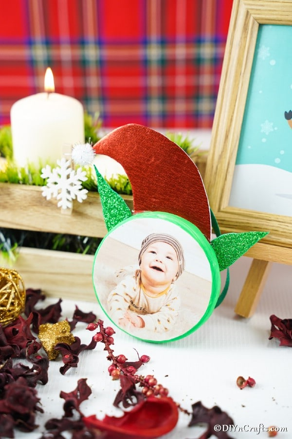 Elf on the shelf ornament displayed on a table in front of plaid background