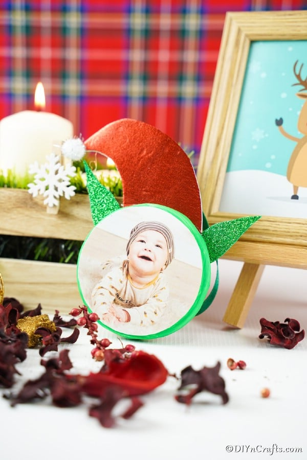 An elf ornament sitting with other holiday decorations in front of a plaid background