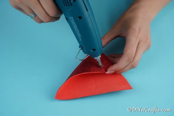 Gluing the foam board pieces together to create cone hat for Christmas gnome