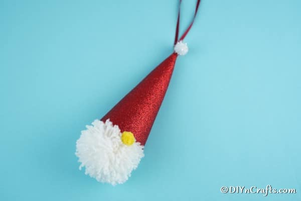 A simple Christmas gnome ornament decoration laying on a blue surface