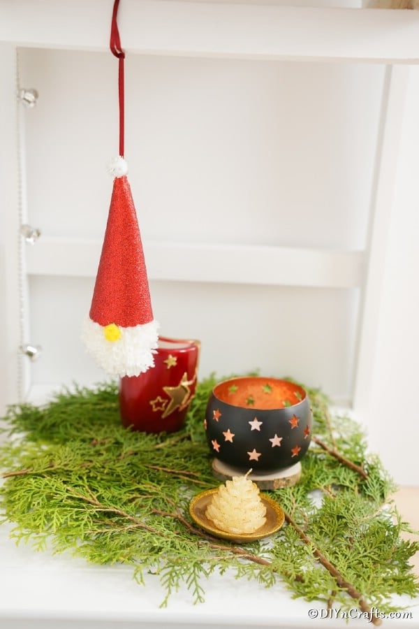 A Christmas gnome ornament hanging on a shelf above holiday decorations