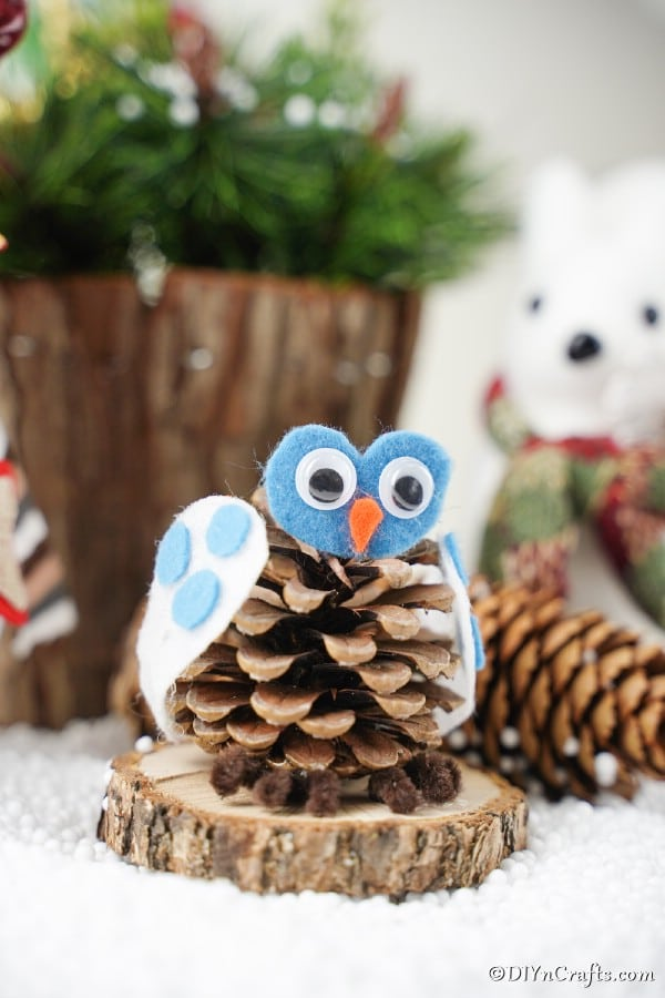 A pinecone owl decoration sitting on a wood slice