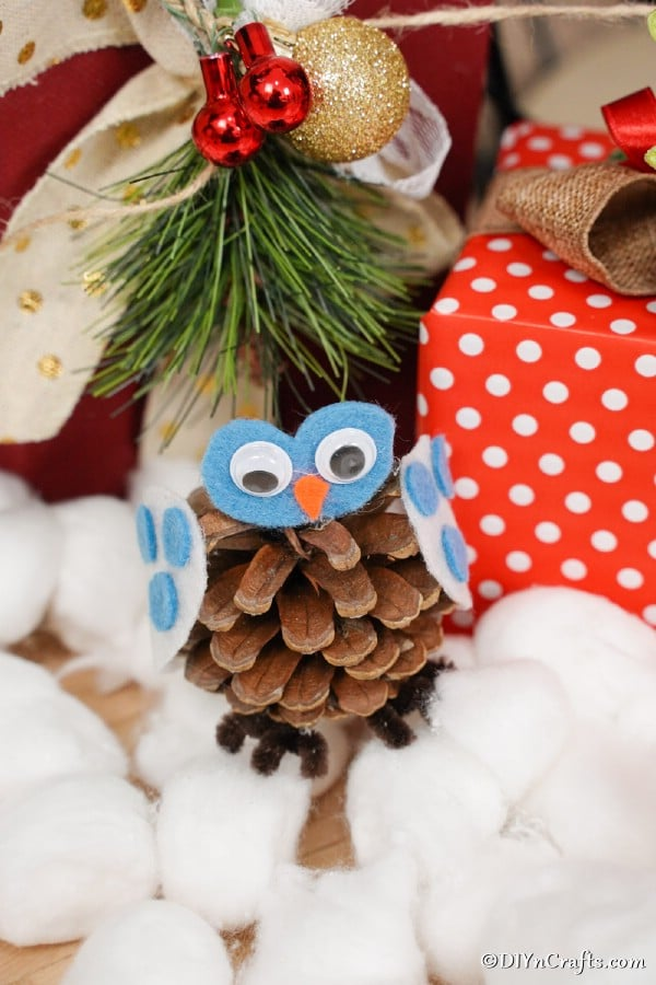 A pine cone owl decoration sitting on cotton balls in front of presents