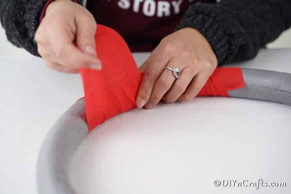 Adding red fabric to a diy Christmas wreath