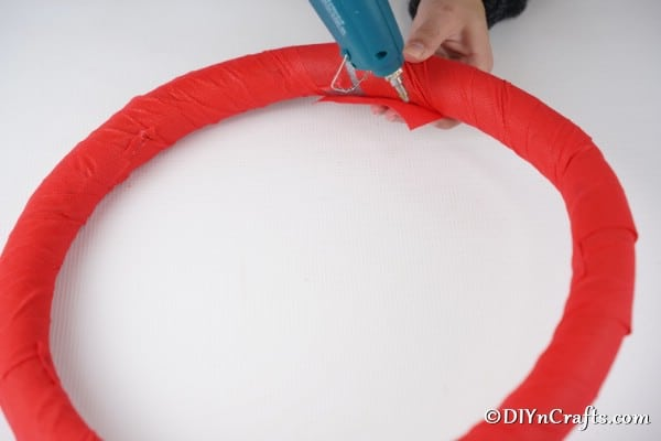 Securing red fabric to the rustic wreath