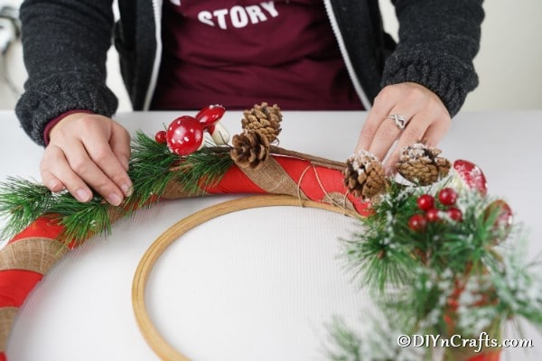 Decorating the holiday wreath with greenery and berries