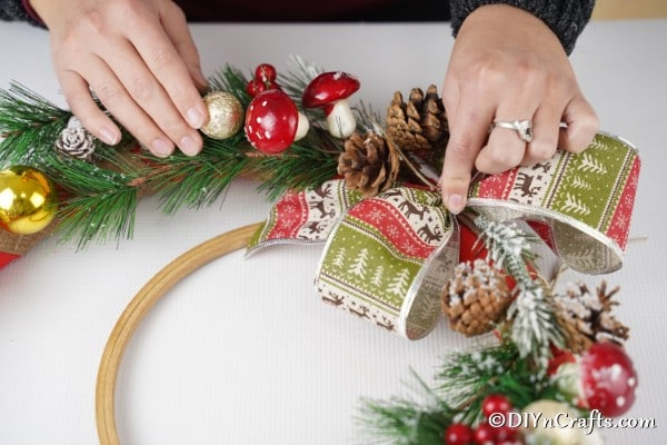 Adding a bow to the rustic DIY Christmas wreath