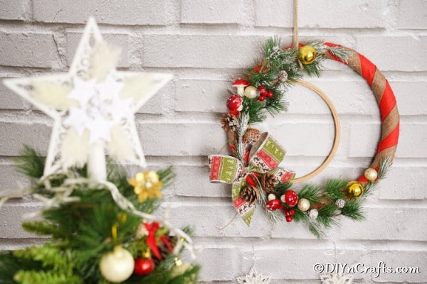 A rustic Christmas wreath behind a Christmas tree on a brick wall