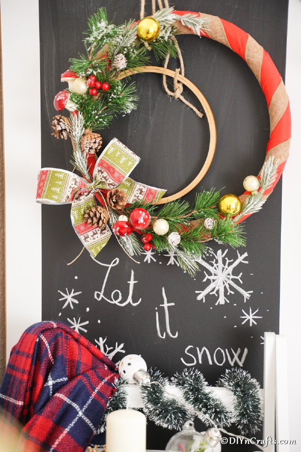 A rustic diy Christmas wreath hanging against a chalkboard sign