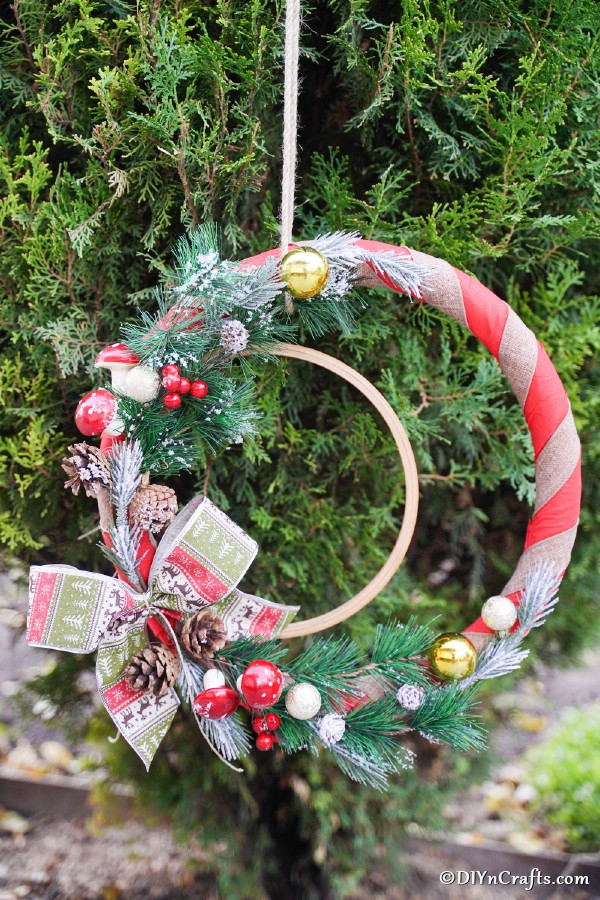 A rustic diy Christmas wreath hanging on a cedar bush outside