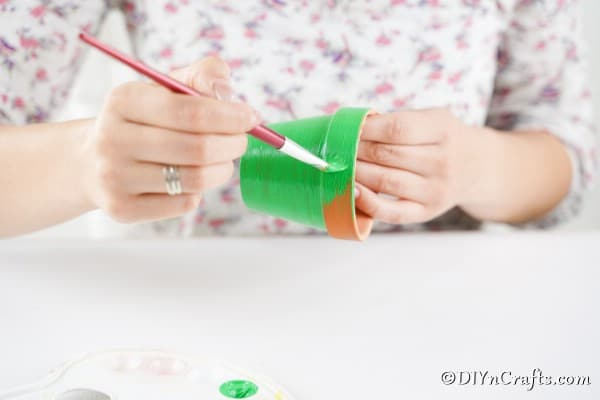 Painting flower pot green to make a bell