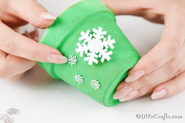 Gluing snowflake decorations to the side of the holiday bell craft