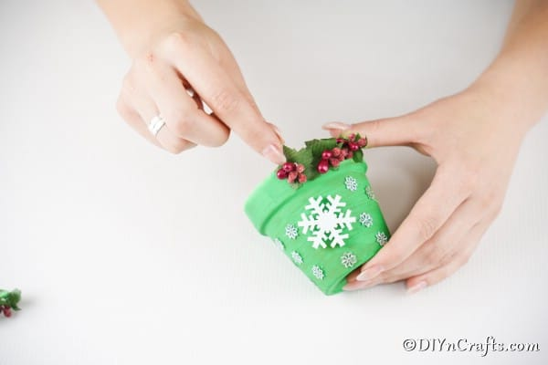 Gluing holiday berries and leaves onto bottom of flower pot Christmas bell decoration