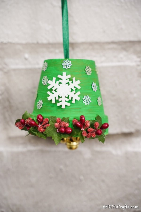 DIY Christmas Bell hanging against white brick wall