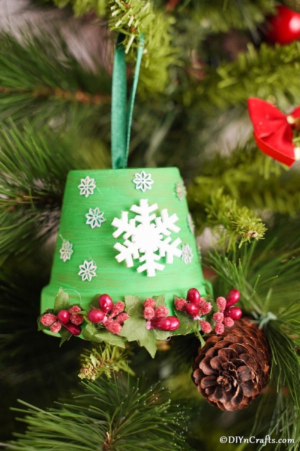 A DIY Christmas bell decoration hanging in a Christmas tree