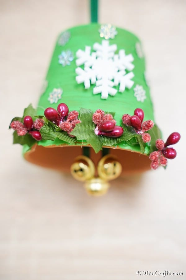 A green christmas bell decoration against white background