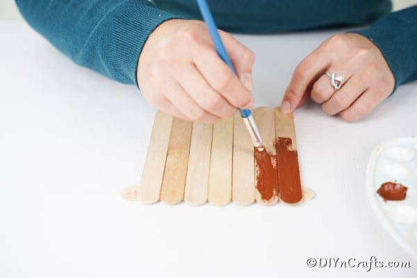 Painting craft sticks for making a gingerbread house