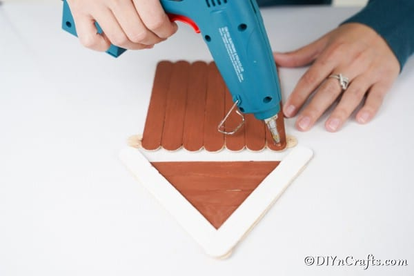Gluing a roof onto the popsicle stick gingerbread house ornament