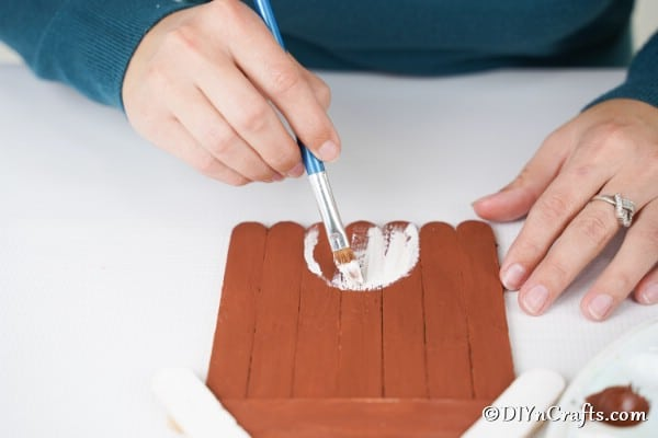 Painting a door onto the craft stick gingerbread house decoration