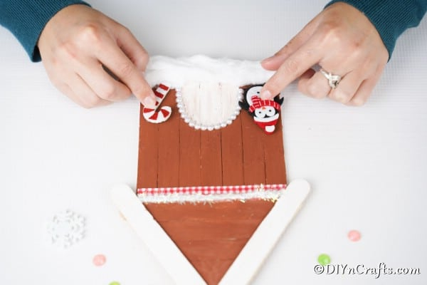 Adding candy cane and penguins to the gingerbread house craft