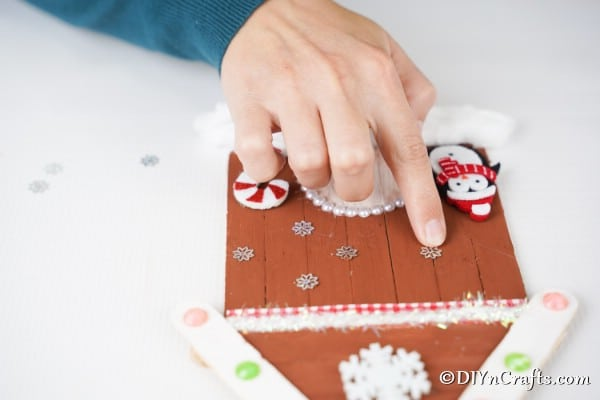 Adding snowflake stickers to the front of the craft stick gingerbread house