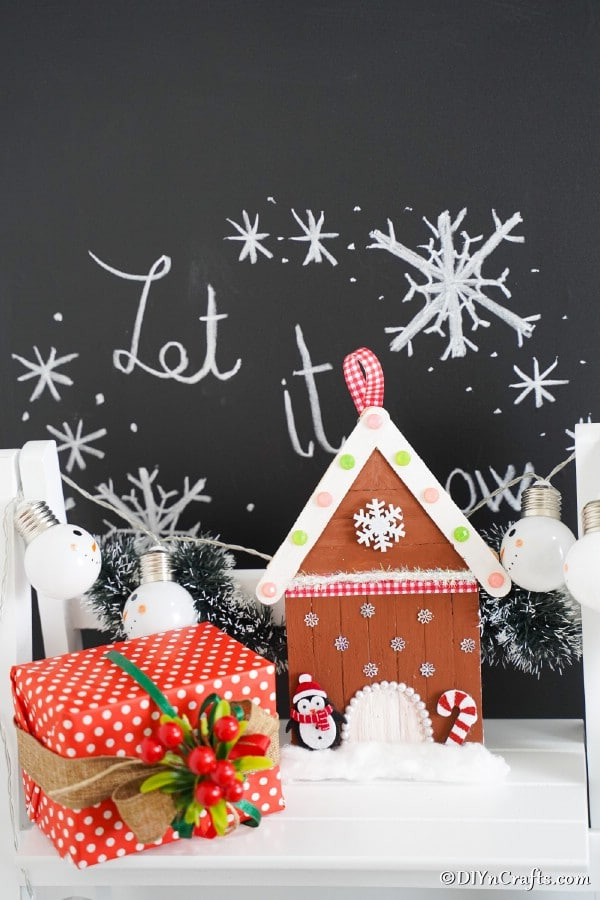 Gingerbread house decoration on a white shelf in front of holiday sign