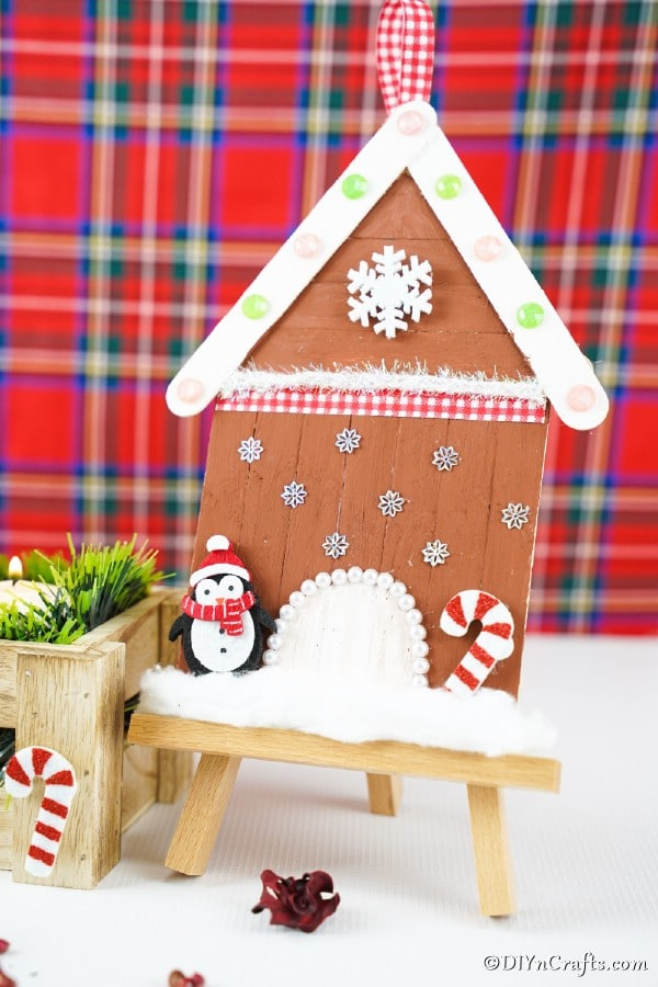 Popsicle stick gingerbread house in front of plaid backdrop