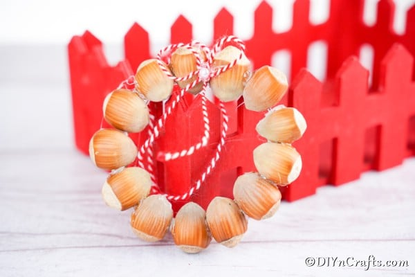 Rustic hazelnut wreath ornament sitting in front of a red wooden box