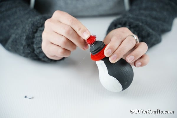 Gluing a red pom pom on top of a light bulb penguin decoration