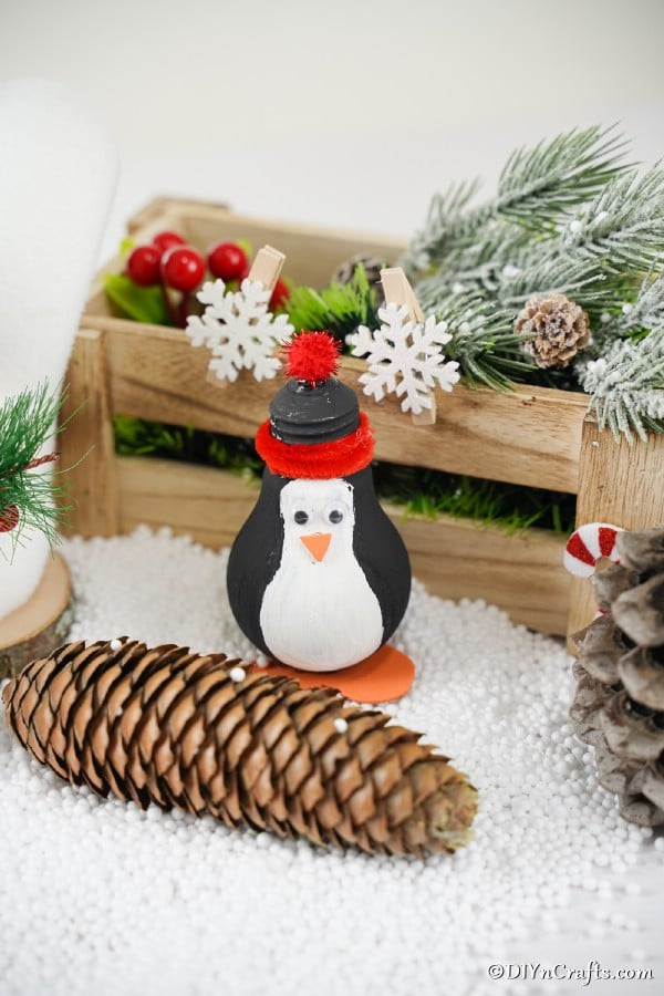 A penguin lightbulb ornament in front of a wooden box filled with holiday decorations
