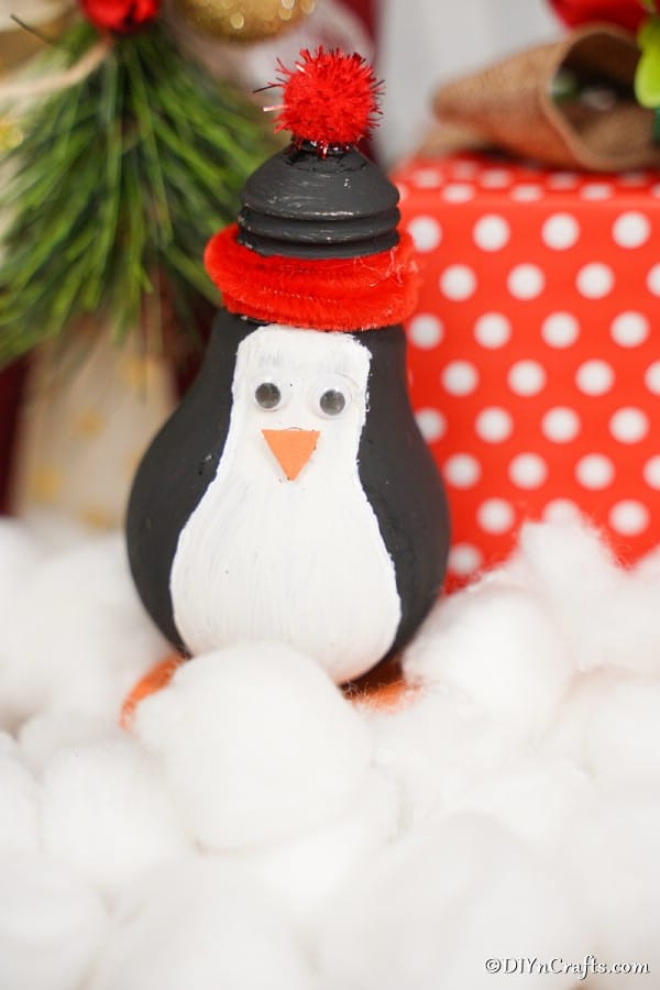 A light bulb penguin sitting in front of a red and white present and on top of cotton balls