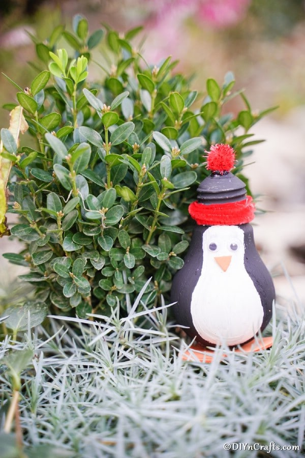 A penguin decoration in front of greenery