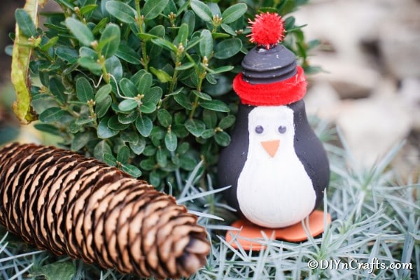 A penguin decoration on a bed of hay with pinecone next to it