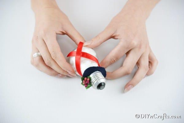 Gluing a ribbon onto a light bulb snowman to create a scarf