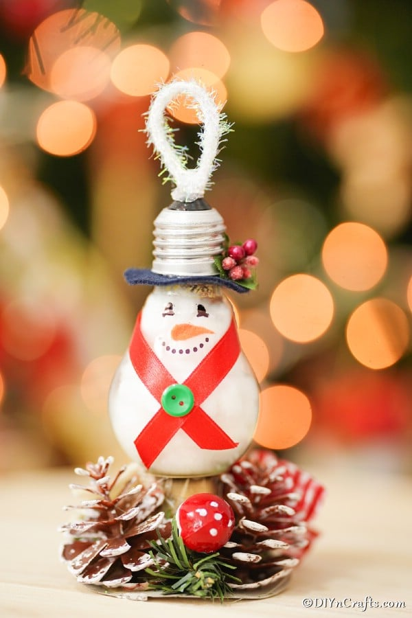 A light bulb snowman ornament hanging in front of a christmas tree