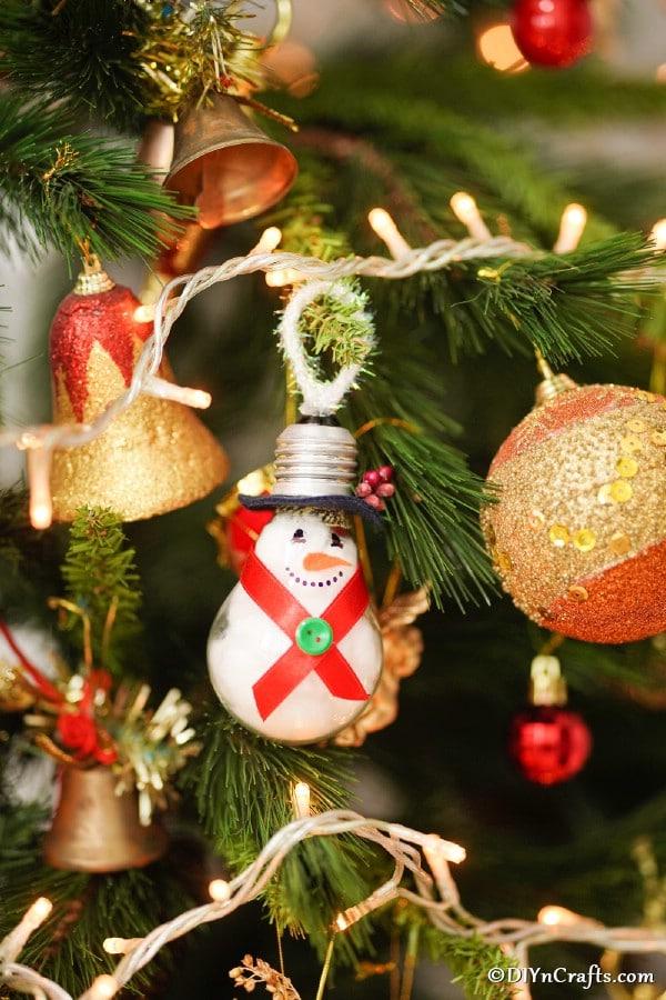 Light bulb snowman ornament on a Christmas tree