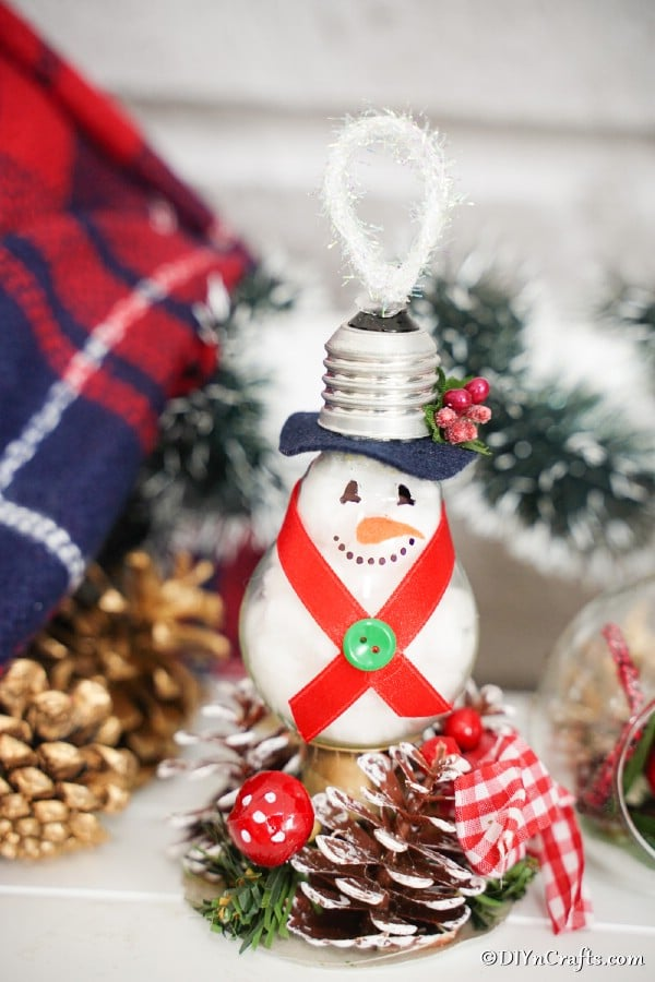 A light bulb snowman ornament on a table in front of holiday decorations