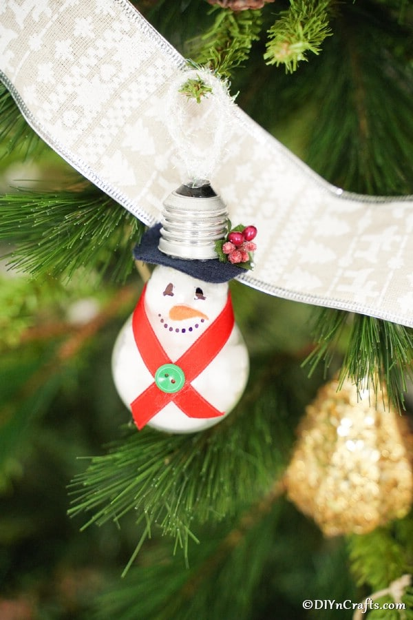 Light bulb snowman ornament hanging on a Christmas tree
