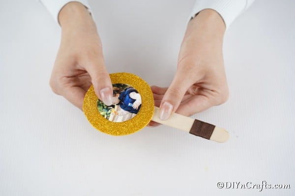 Gluing the glitter paper and picture onto the lollipop photo ornament
