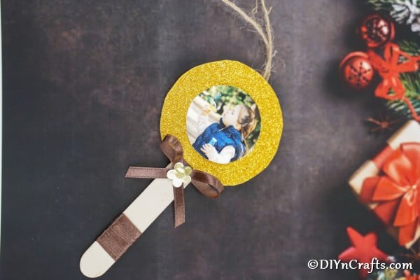 A lollipop photo ornament on a black surface with holiday decor