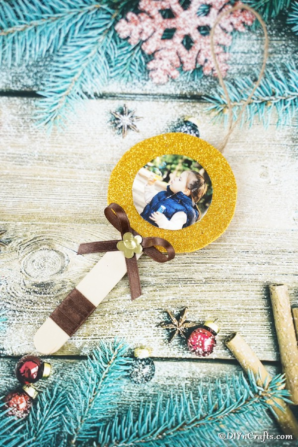 A craft stick lollipop photo ornament laying on a wooden surface with blue and silver holiday decor