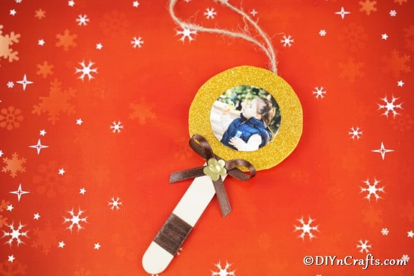 A craft stick lollipop photo ornament laying on an orange paper with stars