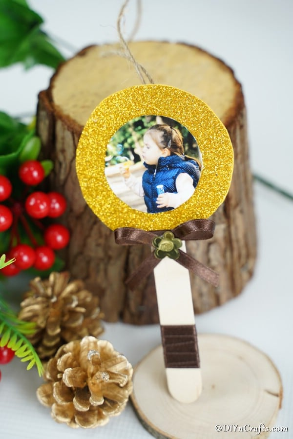 Craft stick lollipop Christmas ornament sitting on a table with other holiday ornaments