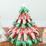 A paper strip Christmas tree displayed next to other holiday decor pieces
