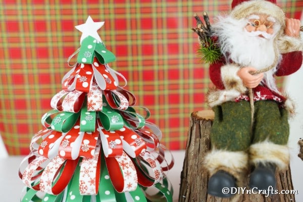 A mini paper strip Christmas tree in front of red plaid background