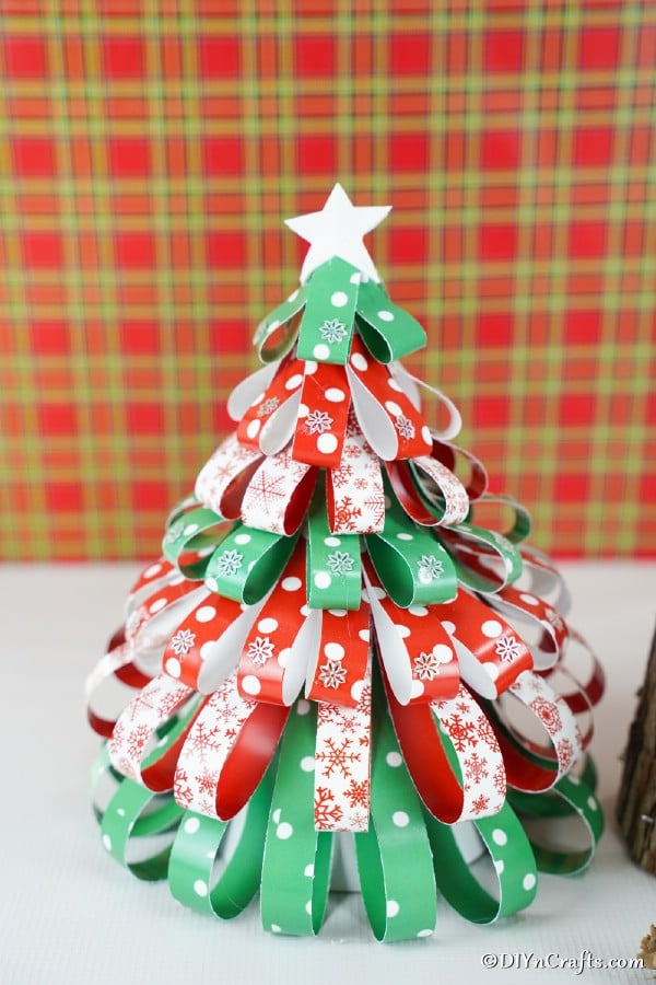 A mini paper strip Christmas tree decoration in front of a plaid background